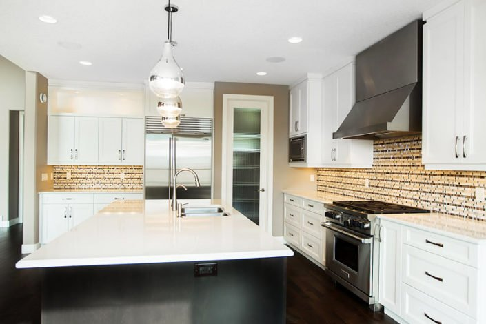 The Windsor - Kitchen - The mosaic stone, glass and metal backsplash add sparkle to this space and compliment the stainless steel appliances and chrome island pendant fixtures.