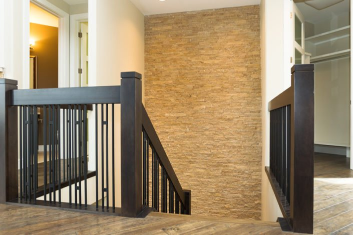 The Stratton - Stair Feature Wall - The floor to ceiling cream stone wall add contrast to the chocolate and metal railing.