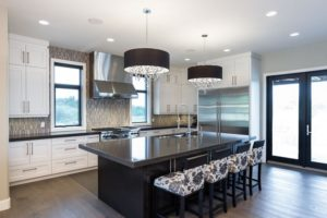 "The Soho II – Kitchen – Custom cabinetry is contrasted with charcoal 2 ½"" quartz countertops. A taupe stone and glass backsplash and bejewelled black drum pendant lights add drama to this space. A large dining room directly off the kitchen makes dinner time accessible and easy."