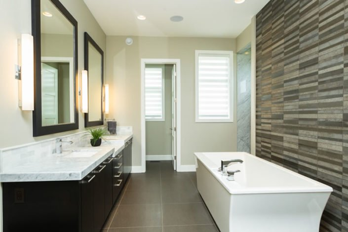 "The Soho II – Ensuite – The free standing tub is backed on to an impressive 13' x 4' marble his/hers shower enclosure. Dark stained custom cabinets are contrasted by the Carrera marble 2 ½"" countertop. A spacious walk in closet is located directly beside the ensuite for ease of accessibility."