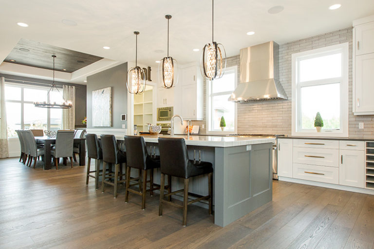 The Manor - Kitchen - Above the charcoal island are 3 black iron pendant light fixtures wrapped around a sparkling string of chrome and crystal.