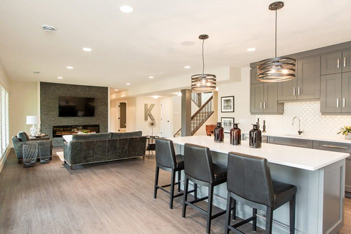 "The Manor – Basement – The full height windows spread light throughout this open concept main area. The Bluestone fireplace surrounds a 72"" linear fireplace and is adjacent to a custom grey bar with white quartz countertops, dishwasher and fridge."