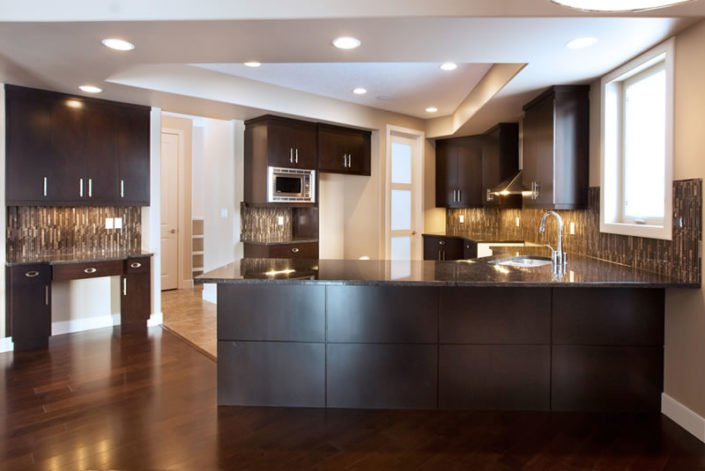 The Manchester - Kitchen - This functional kitchen is both beautiful and functional. The large peninsula allows space for many cooks in the kitchen; the separate desk area keeps home organization neatly away.