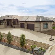 The Manor – Exterior – Black triple pane windows. Acrylic stucco & stone exterior. Black rubber shake style roof. Aggregate concrete driveway. Oversized, 4 car garage. Low maintenance Epoxy garage floor finish. Two floor drains. Garage is radiant heated.